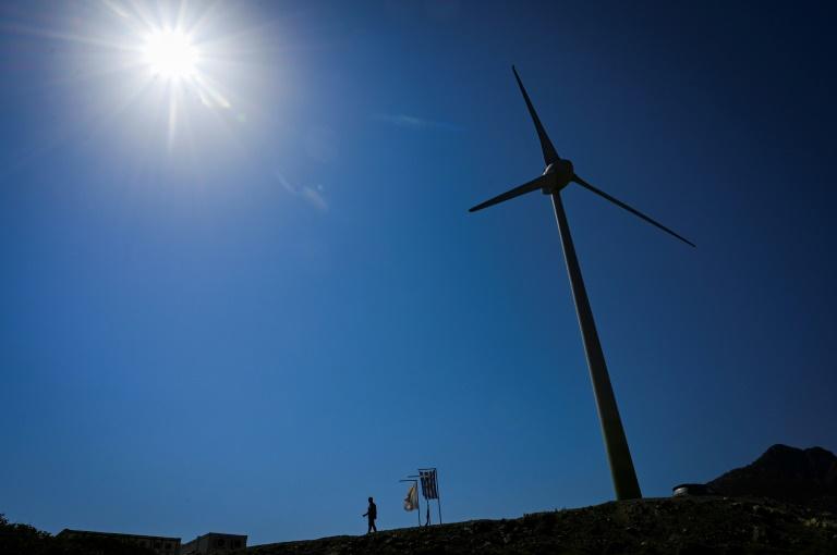 Un homme marche à côté d'une éolienne sur l'île grecque de Tilos. (AFP)